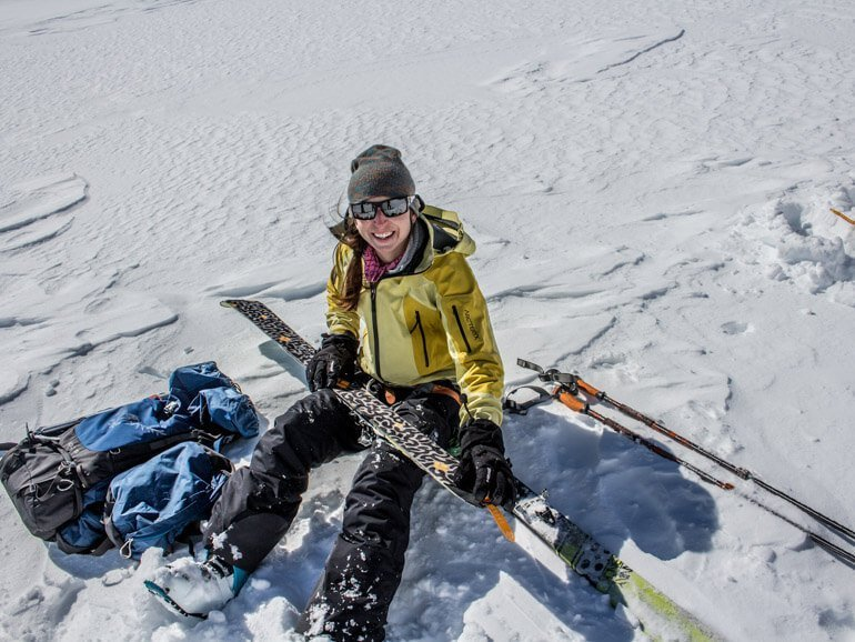 Woman sitting in snow on 3 Day Backcountry Skiing trip