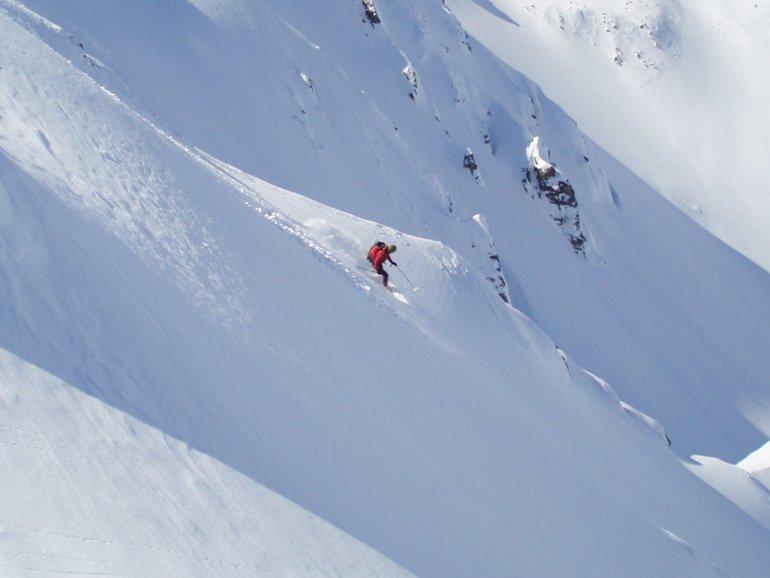 Skier coming down steep slope