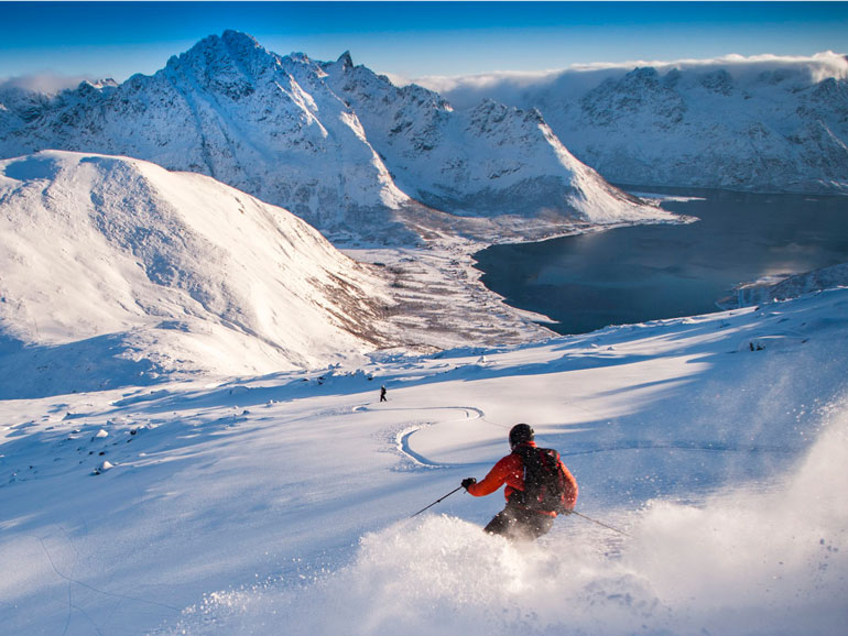 Man skiing by rocky mountain